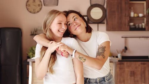 Two women friends hugging at home. Adorable lesbian couple.
