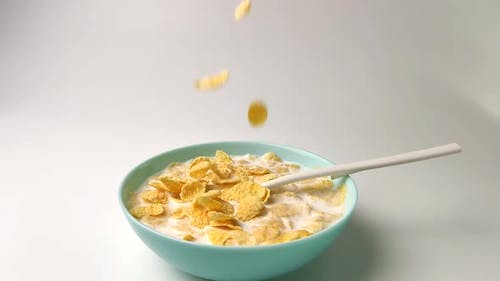 Stir Cornflakes with Milk, Healthy Breakfast, Slow-motion Shooting on a White Background.