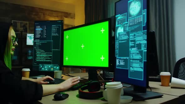 Thumbnail for Zoom in Shot of Hacker Girl in Front of Computer with Green Screen