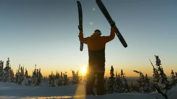 Thumbnail for Sportsman Shakes Skies on Snowy Mountain Top Against Sunset