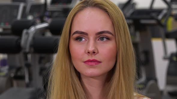 Thumbnail for Eine junge schöne Frau sieht sich um in ein Fitness-Studio - Gesicht Nahaufnahme