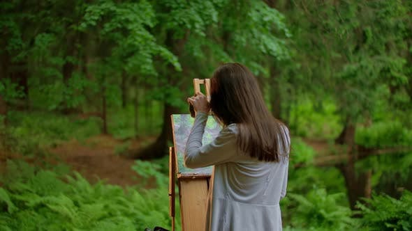 Thumbnail for Rear View of a Young Artist Woman Painting a Landscape in a Summer Forest