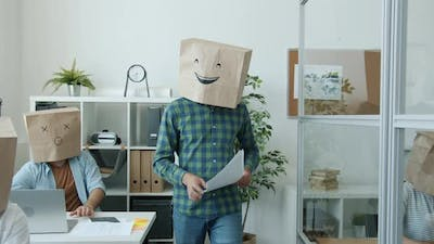 Businesspeople with Paper Bags on Heads Showing Emoji Busy with Paperwork in Office