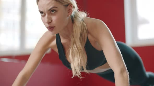 Fitness Woman Pushing Up Exercise on Floor in Sport Club
