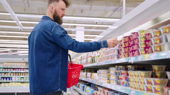 Male Shopper is Choosing Yogurt for Breakfast and Lunch Shopping in Supermarket