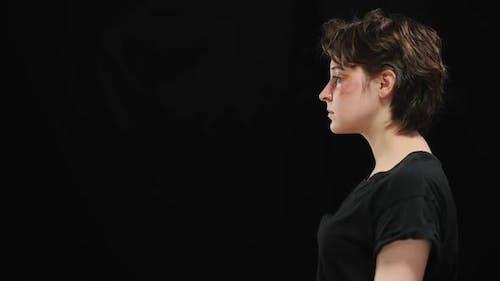 Seitenansicht einer jungen Frau mit geschlagenem Gesicht bei Prellungen auf der rechten Seite auf schwarzem Hintergrund