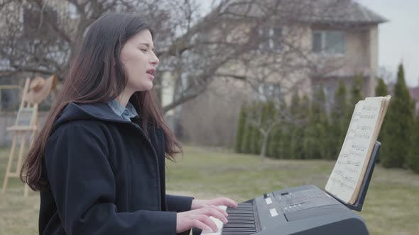 Thumbnail for A Successful Brunette Girl Plays on a Synthesizer and Sings While Sitting in the Backyard