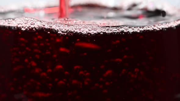 Pouring and splashing red wine in big wineglass
