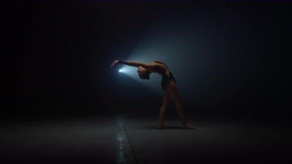 Flexible Girl Doing Somersault in Dark Space in Dark Space