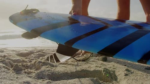 Male surfer picking up surfboard on beach in the sunshine 4k