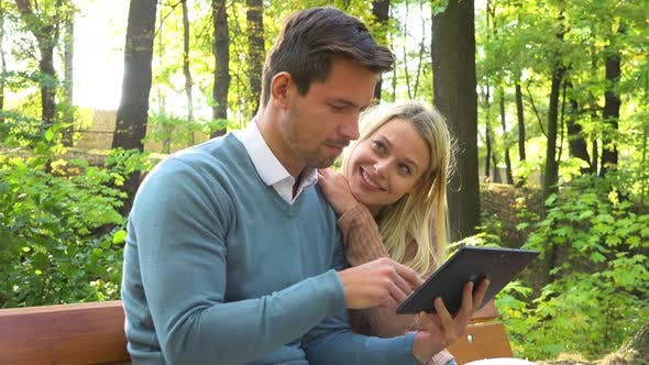 Thumbnail for A Young Attractive Couple Looks at a Tablet on a Bench in a Park on a Sunny Day - Closeup