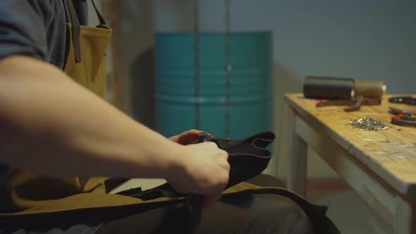 Schuhmacher verarbeitet die Haut. Arbeiten mit Zangen