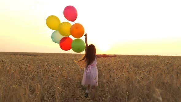 Thumbnail for Young Girl In The Dress With Colorful Ballons Is Running Across The Field