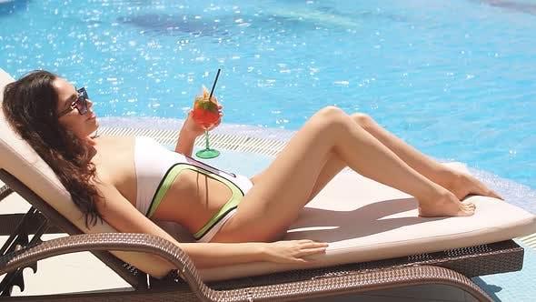 Thumbnail for Young Beautiful Woman in Bikini Lying on Sunbed in Hotel Pool Side Area