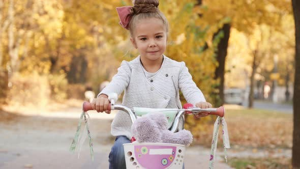 Little Girl Rides Bicycle on Autumn City Boulevard