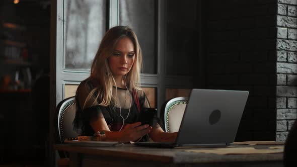 Cover Image for Freelancer Woman Working with a Laptop in a Coffee Shop, Close Up View