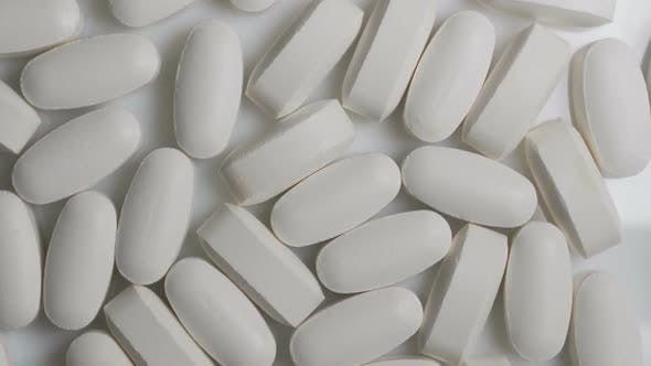 Thumbnail for Close Up of White Capsules Rotate on Table. Pharmacy Antibiotic Pills