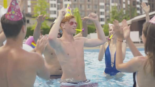 Thumbnail for Young Redhead Man Celebrating Birthday with Friends in Pool. Portrait of Happy Young Caucasian Guy