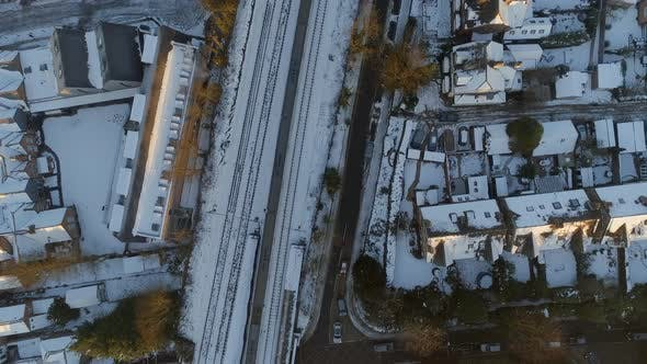 Commuter Train Departing a Snowy Urban Station