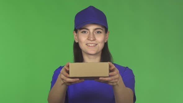 Thumbnail for Happy Delivery Woman Smiling Holding Out Small Package To the Camera