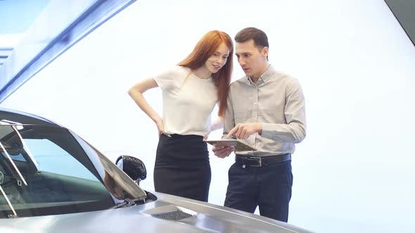 Thumbnail for Young Couple Choosing Luxury Car in Auto Dealership Looking at Interior and Car Features