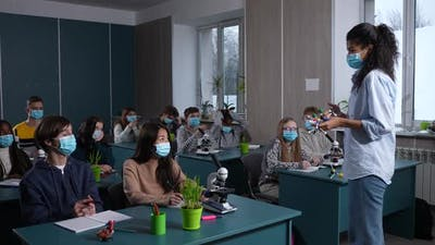 Diverse Pupils in Face Masks Listening to Lesson