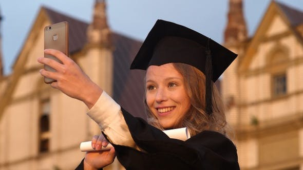 Cover Image for Attractive graduate girl taking selfie on graduation day