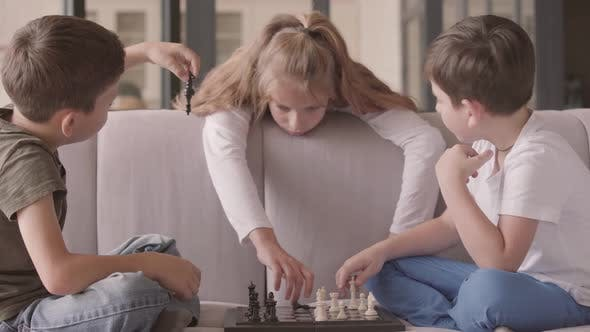 Thumbnail for Kids Playing Chess Sitting on the Couch at Home. Siblings Spending Time Indoors. Happy Family