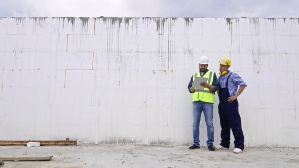 Cover Image for Engineers Standing by Wall and Talking