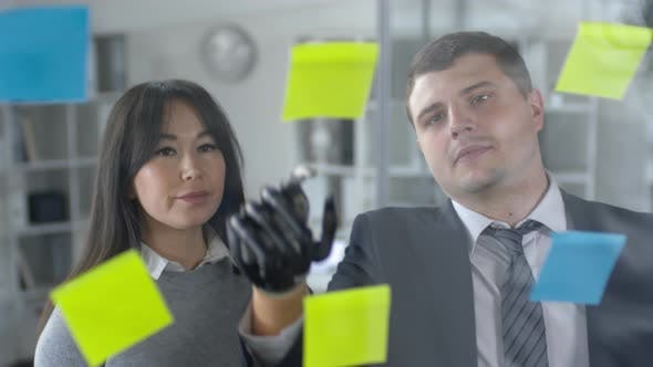 Thumbnail for Man with Bionic Hand Discussing Plans in Sticky Notes with Female Colleague