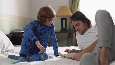 Two Brothers Lie Down in Bed, Older Brother Read for Small Brother a Book