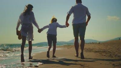 Family running on sandy beach