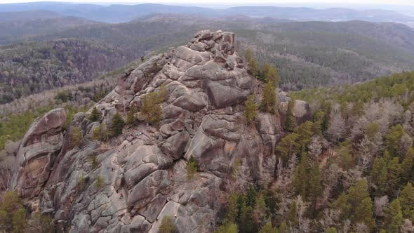 Thumbnail for Aerial Shot of Tourists Climb To the Top of the Rock in the Siberian Natural Park Stolby