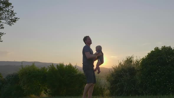 Thumbnail for Wide Shot of a Loving Father and an Adorable Baby Boy Playing Outside