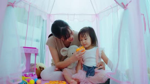 Asian beautiful parent, mother play education game with kid to learn and develop skill in tent.