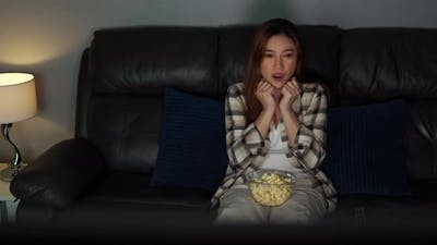 scared young woman is watching horror movie TV on sofa at night