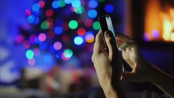Cover Image for Hands with Smartphone on Blurry Lights of Christmas Tree and Fireplace. Gift Order