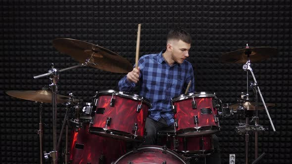 Musician drummer is playing on drum kit in recording studio