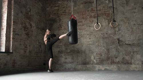 Girl punches and kicks the punches bag in gym. Woman punches and kicks the punches bag