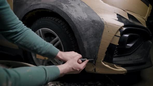 Worker Is Shaping Clay Detail on Car Body in Garage Projecting Tuning for Auto Working By Plastic