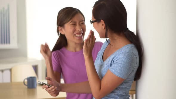 Thumbnail for Excited Chinese businesswomen receiving good news on smartphone