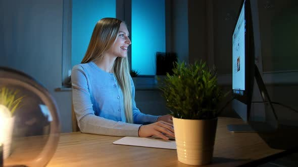 Thumbnail for Smiling Woman Working on Computer at Night. Smiling Female in Checkered Shirt Sitting at Lit By