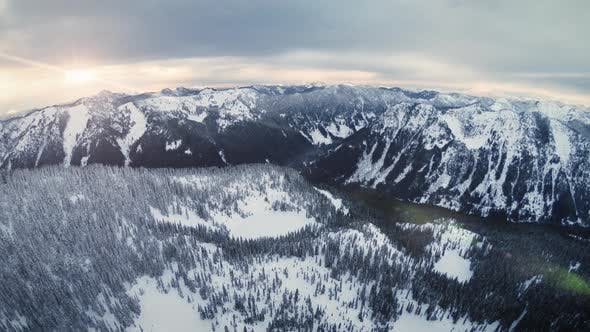 Cover Image for Mountain Range Aerial Background With Winter Snow Flakes Falling