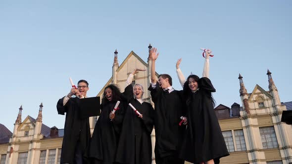 Thumbnail for Graduation Caps Are Tossed Into The Air By A Happy Group Of Student Friends
