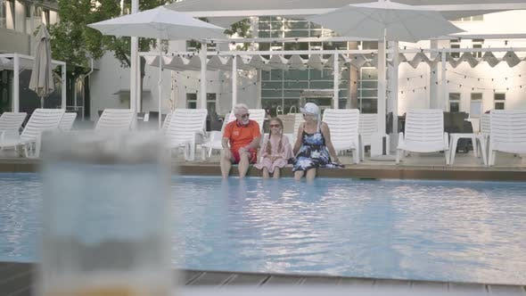 Thumbnail for Fun Happy Mature Couple with Little Granddaughter Sitting on the Edge of the Luxury Pool