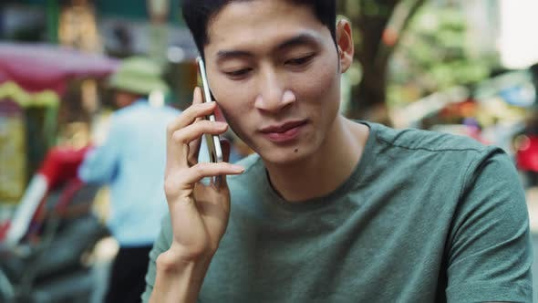 Thumbnail for Handheld view of Vietnamese man is on the phone. Shot with RED helium camera in 8K