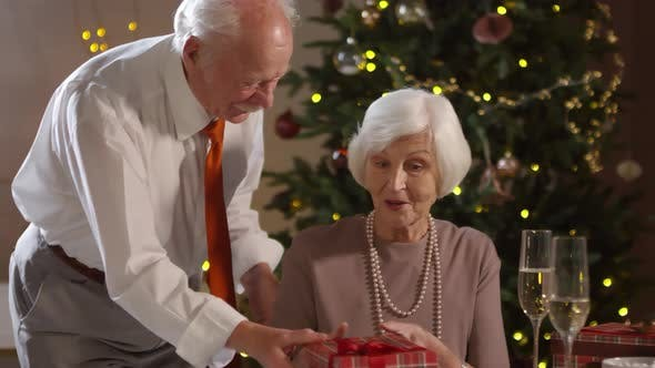 Cover Image for Senior Man Surprising Wife with Present on Christmas