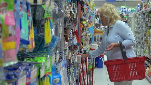 Thumbnail for Senior Woman Is Choosing Household Goods at Supermarket with Shop Basket for Cleaning