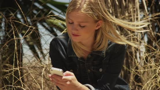Thumbnail for Cute woman texting on smartphone outdoors