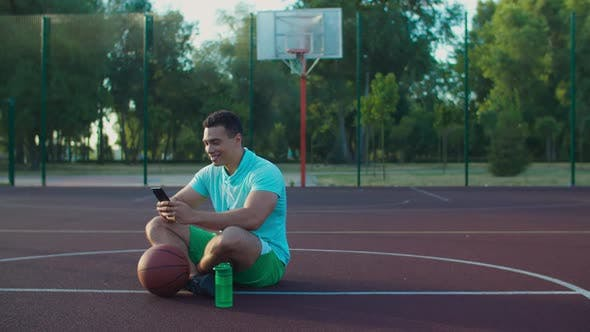Basketball Player Networking with Phone on Court